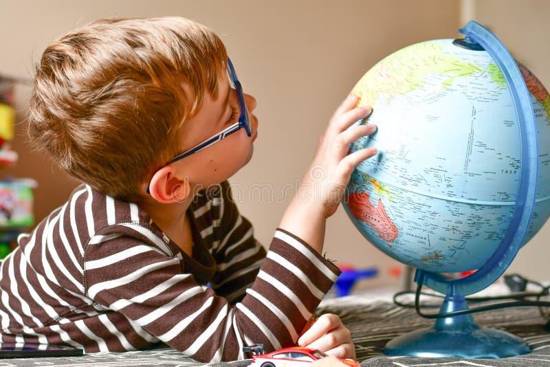 Bambino che impara geografia con il globo a casa immagini stock libere da diritti