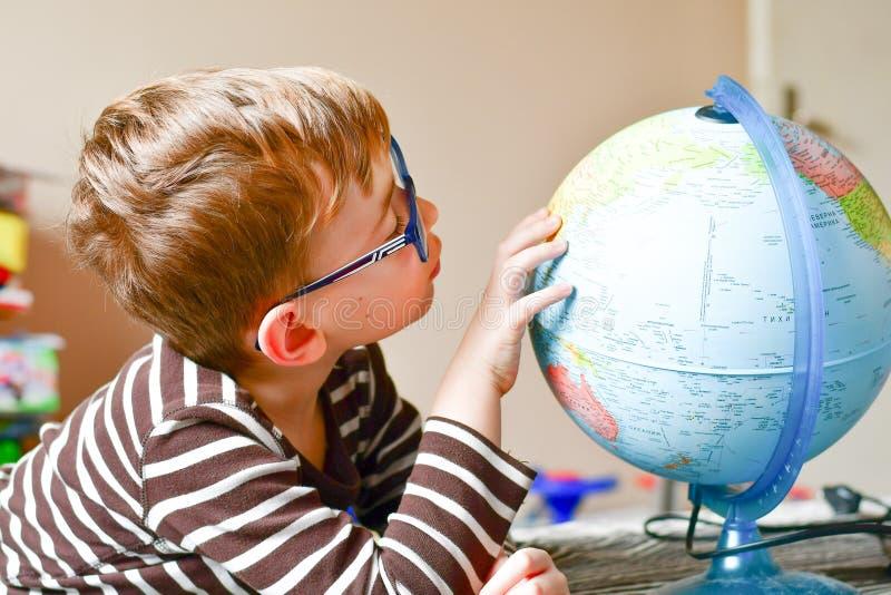 Bambino che impara geografia con il globo a casa immagini stock