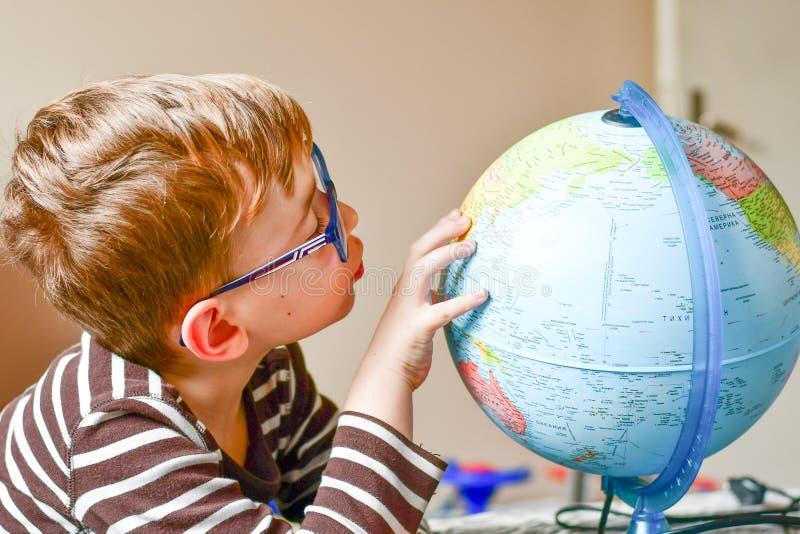 Bambino che impara geografia con il globo a casa fotografie stock libere da diritti