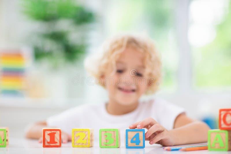 Bambino che impara le lettere Bambino con i blocchetti di legno di ABC immagini stock