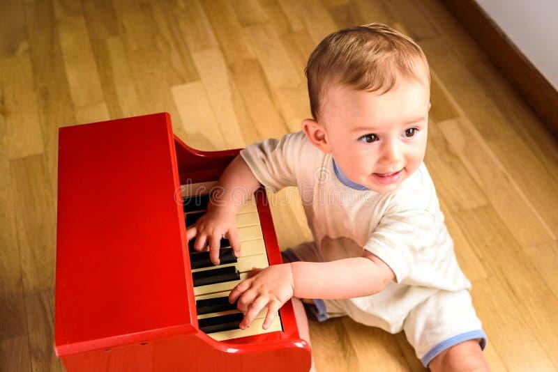 Bambino che impara a suonare il piano con uno strumento giocattolo di legno, una scena d'infanzia tenera e divertente fotografia stock libera da diritti