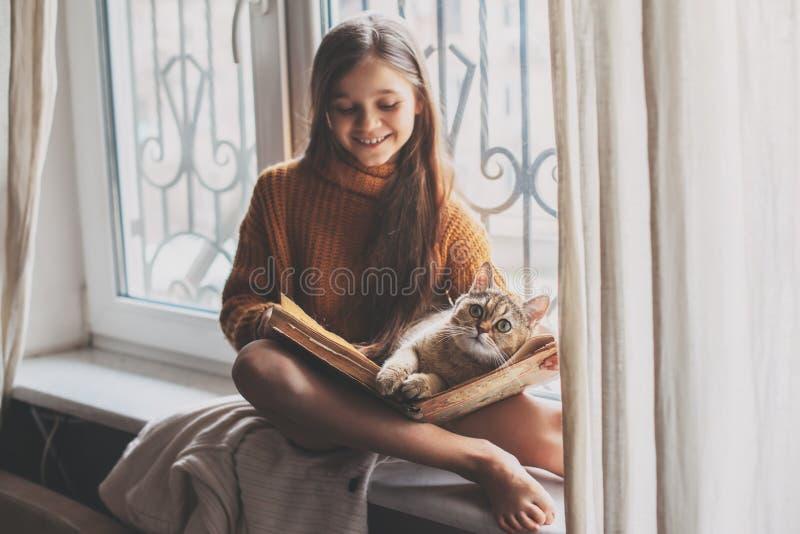 Bambino che legge un libro con il gatto immagine stock libera da diritti