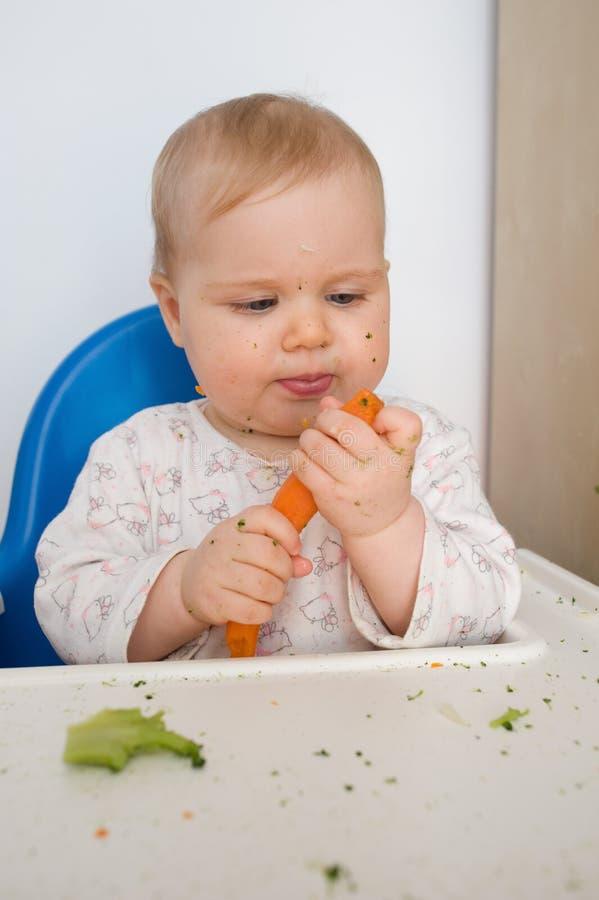 Bambino che mangia carota fotografia stock libera da diritti