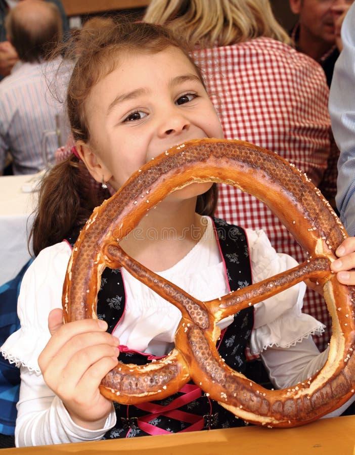 Bambino che mangia ciambellina salata a Oktoberfest, Monaco di Baviera, Germania fotografie stock