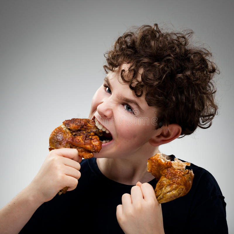 Bambino che mangia coscia di pollo fotografia stock libera da diritti