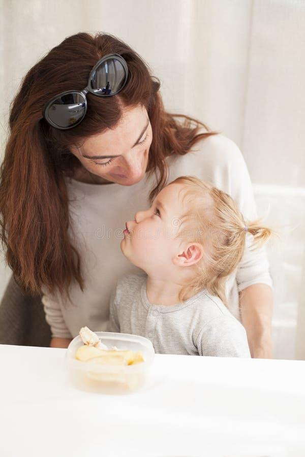 Bambino che mangia e che guarda madre immagini stock libere da diritti