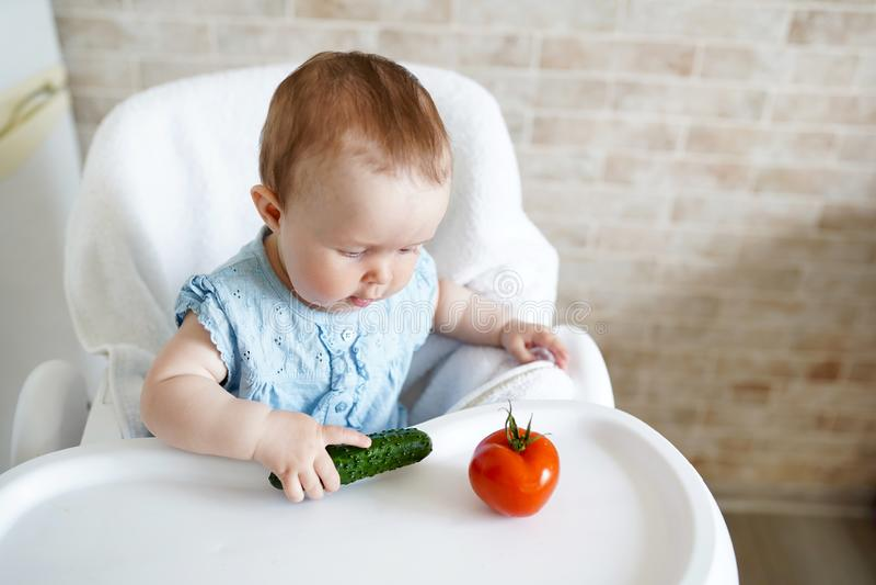 Bambino che mangia le verdure cetriolo verde in mano della bambina in cucina soleggiata Nutrizione sana per i bambini Spuntino o  immagine stock libera da diritti