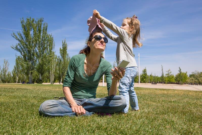 Bambino che mette un cappello sulla madre con il telefono nel parco immagini stock