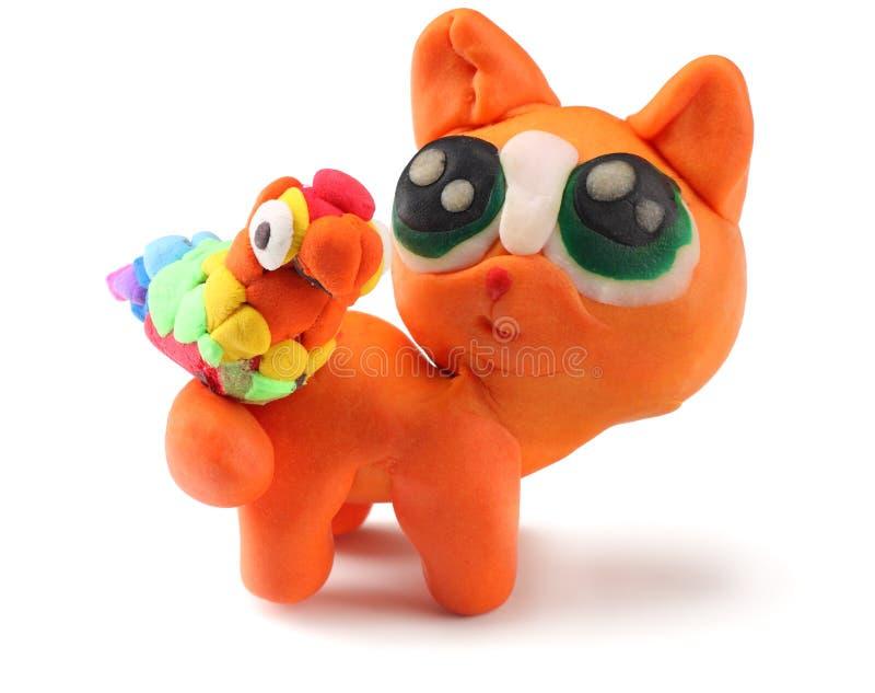 Bambino che modella il gatto dell'argilla con il pappagallo su fondo bianco immagini stock