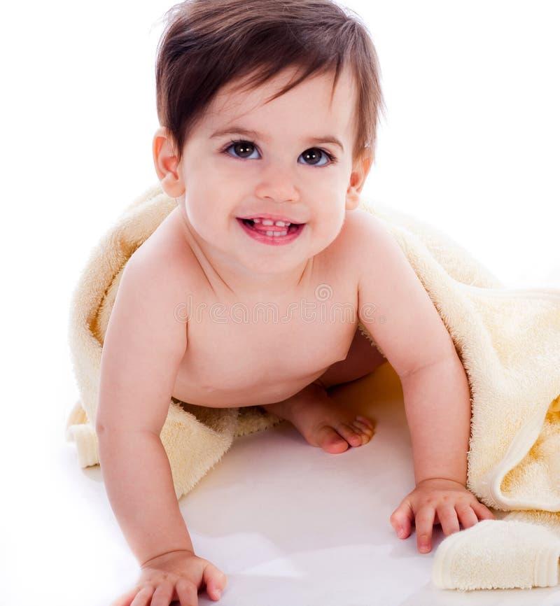 Bambino che mostra i sui denti sotto il tovagliolo giallo immagini stock libere da diritti