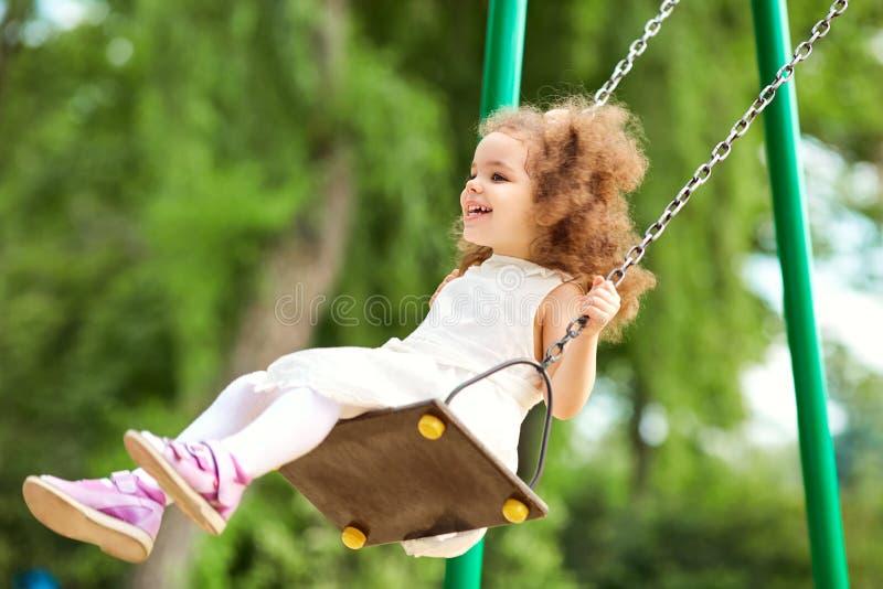 Bambino che oscilla su un'oscillazione al campo da giuoco nel parco fotografia stock