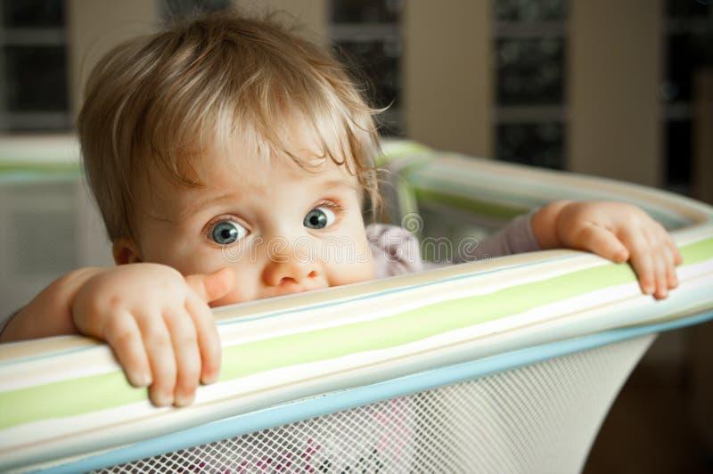 Bambino che osserva sopra il playpen fotografia stock libera da diritti