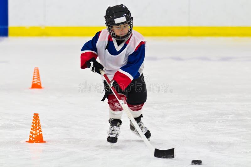 Bambino che pattina con un disco alla pratica del hockey su ghiaccio immagine stock libera da diritti
