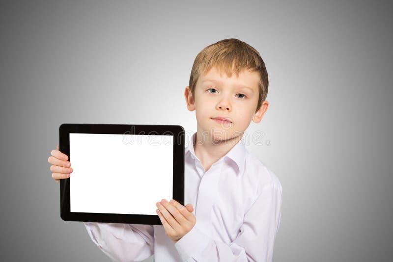Bambino che per mezzo di un PC della compressa immagine stock