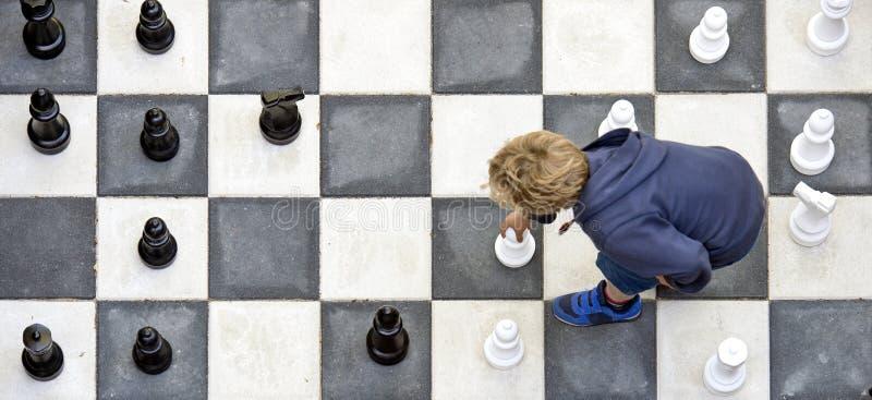 Bambino che playuing scacchi all'aperto fotografie stock libere da diritti