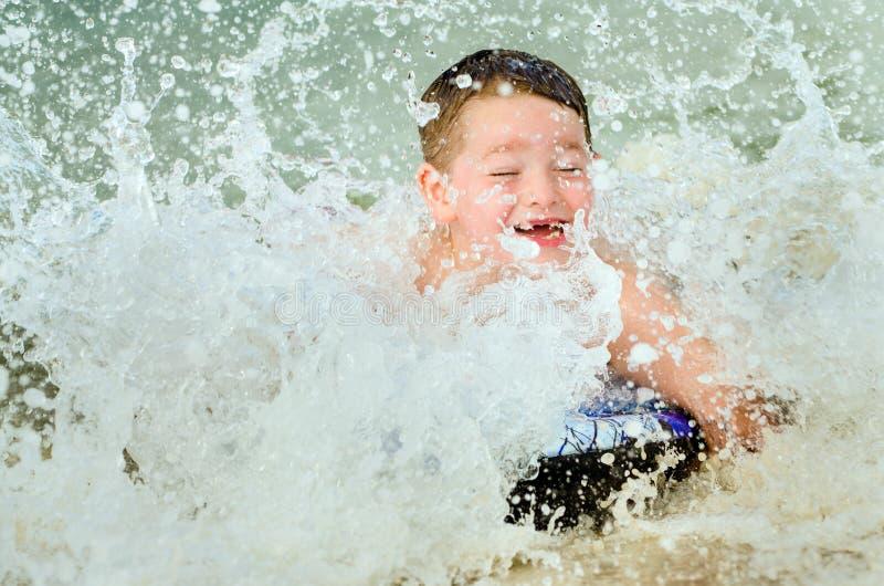 Bambino che pratica il surfing sul bodyboard alla spiaggia fotografia stock