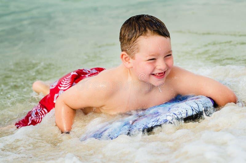 Bambino che pratica il surfing sul bodyboard alla spiaggia fotografia stock libera da diritti
