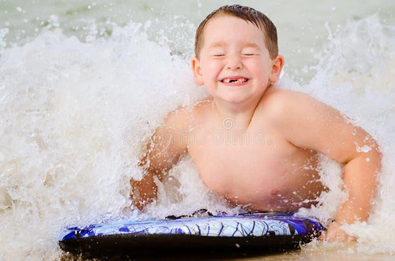 Bambino che pratica il surfing sul bodyboard alla spiaggia immagine stock libera da diritti