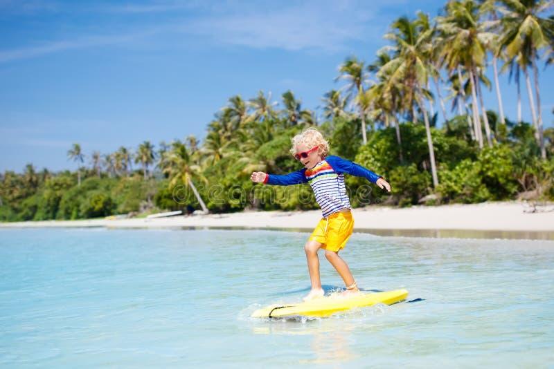 Bambino che pratica il surfing sulla spiaggia tropicale Surfista in oceano immagini stock libere da diritti
