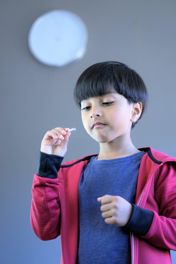 Bambino che prende medicina o le vitamine in tempo immagini stock libere da diritti