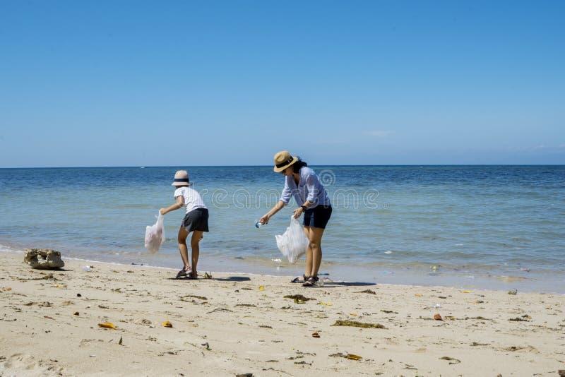 Bambino che pulisce una spiaggia sporca con sua madre fotografia stock