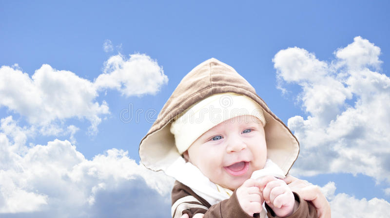 Bambino che ride sui precedenti del cielo fotografia stock libera da diritti