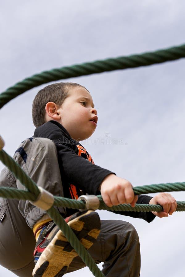 Bambino che scala una funzione della corda immagine stock