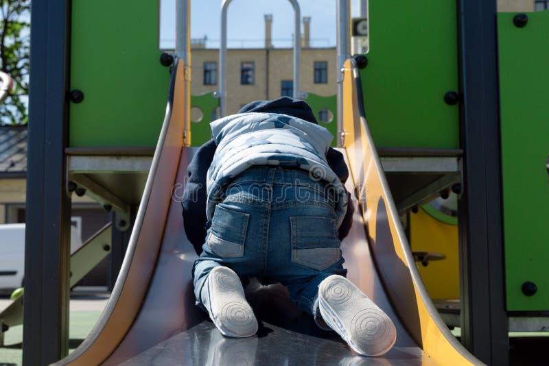 Bambino che scala uno scorrevole in un campo da gioco per bambini fotografia stock libera da diritti