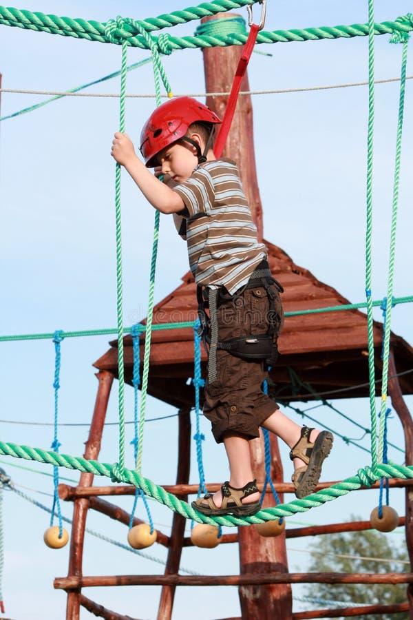 Bambino che si arrampica nel campo da giuoco di avventura fotografie stock libere da diritti