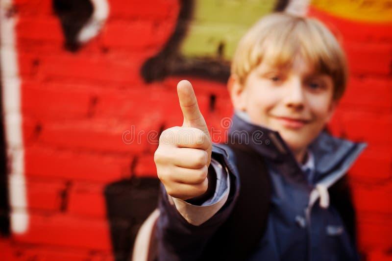 Bambino che si leva in piedi davanti ad una parete dei graffiti fotografia stock