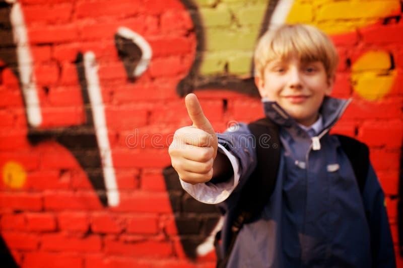 Bambino che si leva in piedi davanti ad una parete dei graffiti immagini stock