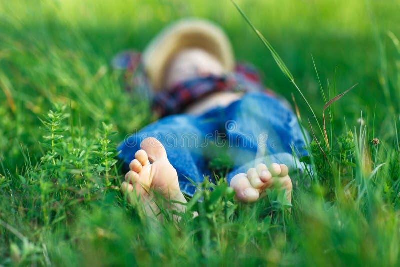 Bambino che si rilassa nell'erba sul campo Fuoco a piedi fotografia stock