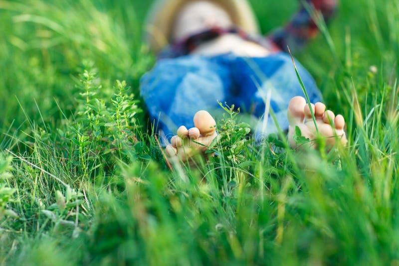 Bambino che si rilassa nell'erba sul campo Fuoco a piedi fotografia stock libera da diritti