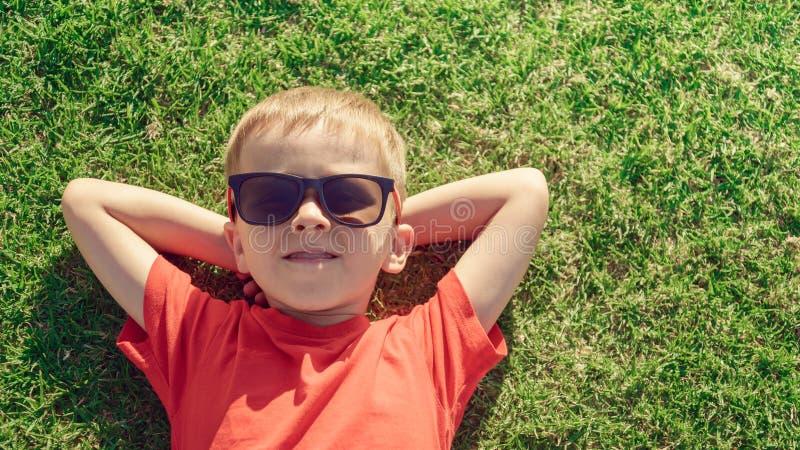 Bambino che si rilassa sull'erba fotografia stock libera da diritti