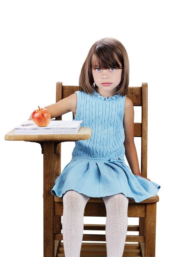 Bambino che si siede allo scrittorio del banco immagini stock libere da diritti