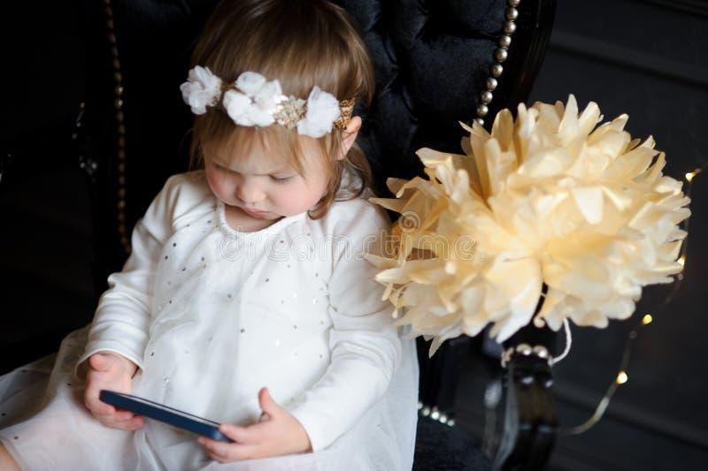 Bambino che si siede nella sedia e che esamina entusiasta lo schermo dello smartphone fotografia stock