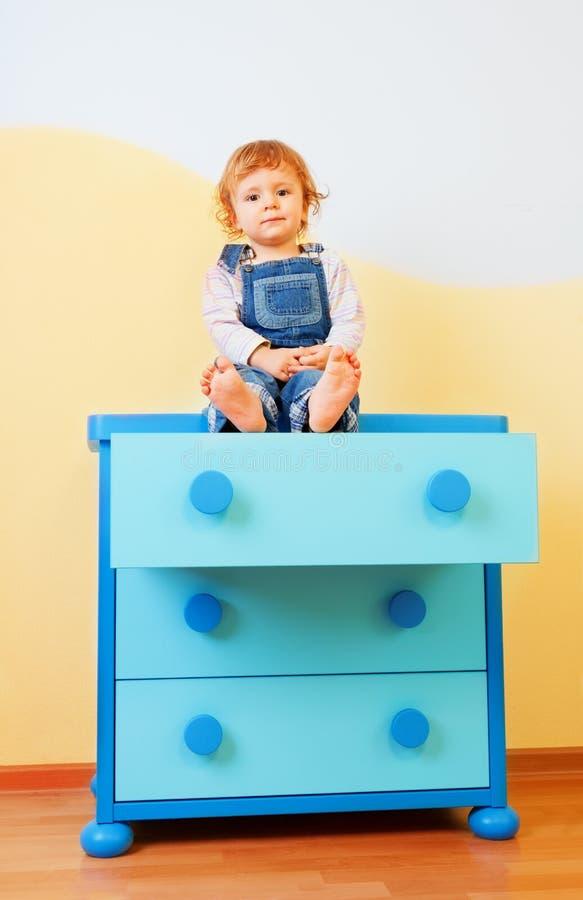 Bambino che si siede sull'armadietto fotografia stock