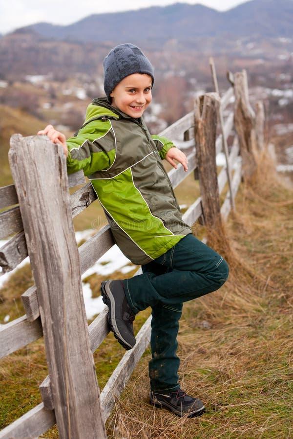 Bambino che si siede sulla rete fissa di legno fotografia stock libera da diritti