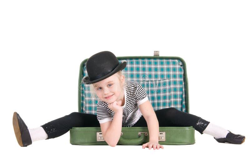 Bambino che si siede in una vecchia valigia verde immagine stock libera da diritti