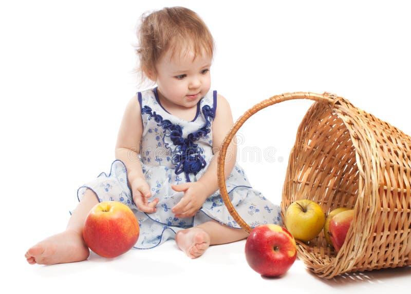 Bambino che si siede vicino al cestino di frutta immagine stock libera da diritti