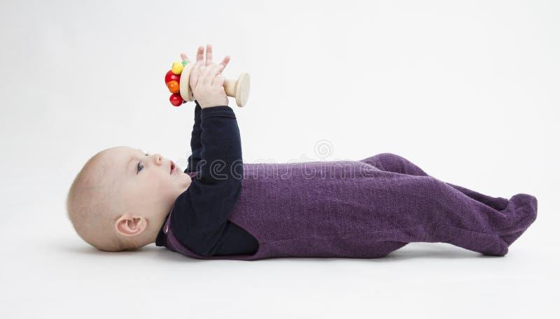 Bambino che si trova sul suo indietro con il giocattolo fotografie stock libere da diritti