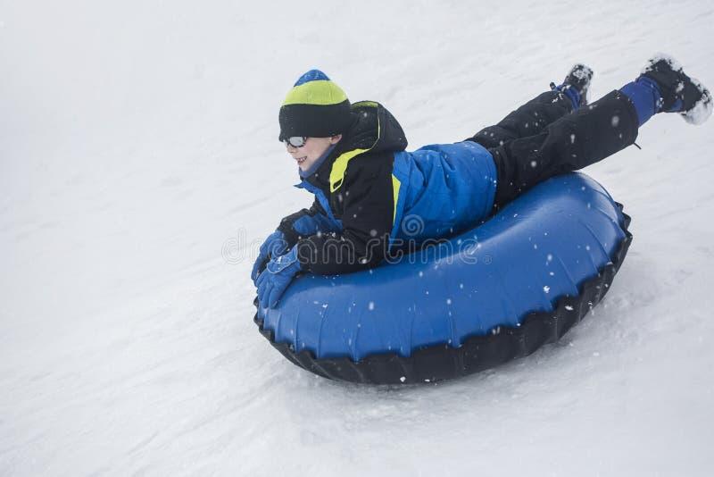 Bambino che sledding giù una collina su un tubo della neve fotografia stock