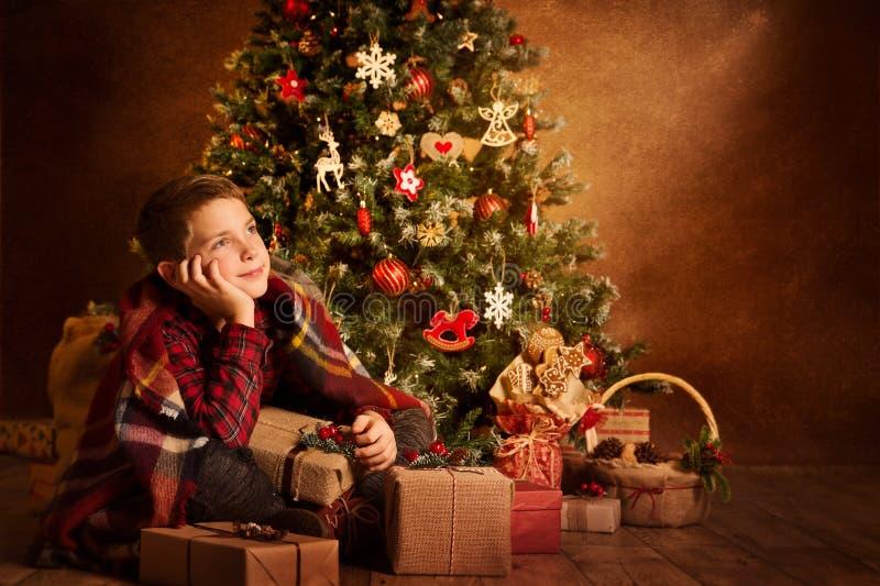 Bambino che sogna sotto l'albero di natale, bambino di Natale del ragazzo del buon anno immagini stock libere da diritti