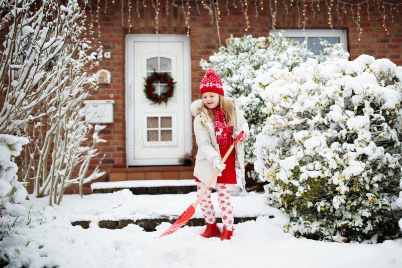 Bambino che spala neve Bambina con la strada privata di schiarimento della vanga dopo la bufera di neve di inverno  fotografia stock