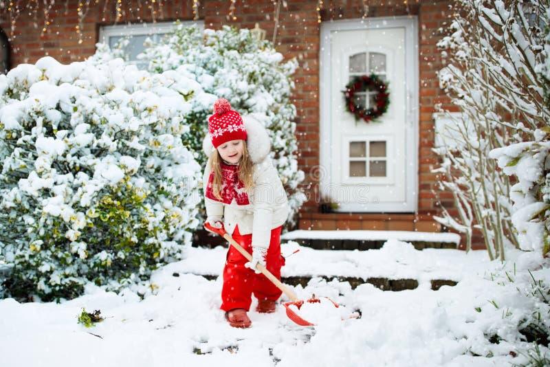 Bambino che spala neve Bambina con la strada privata di schiarimento della vanga dopo la bufera di neve di inverno  fotografie stock