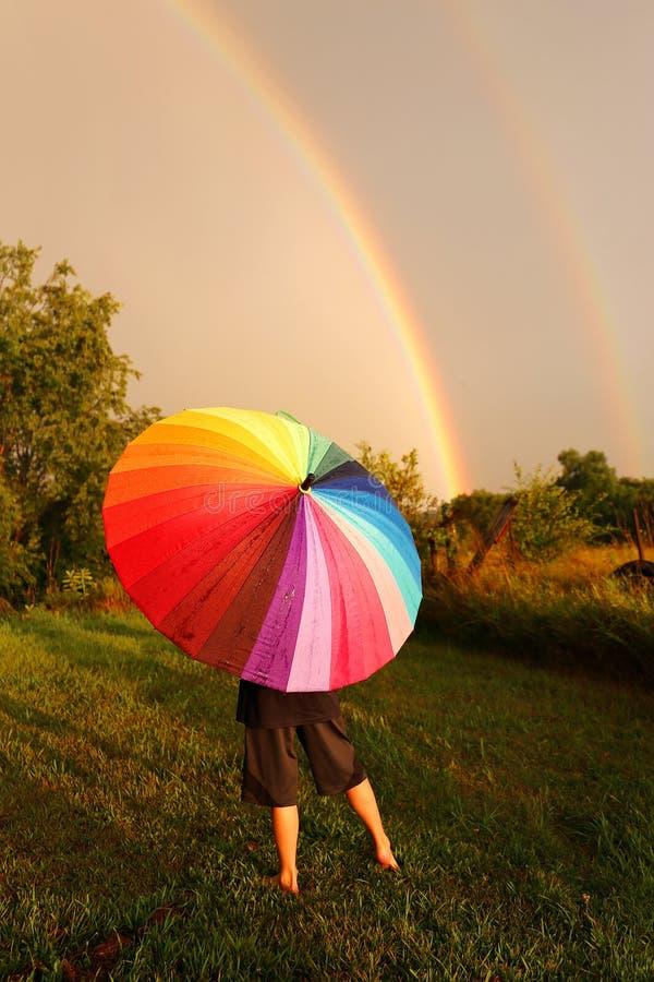 Bambino che sta in pioggia con l'ombrello variopinto che esamina doppio immagine stock libera da diritti