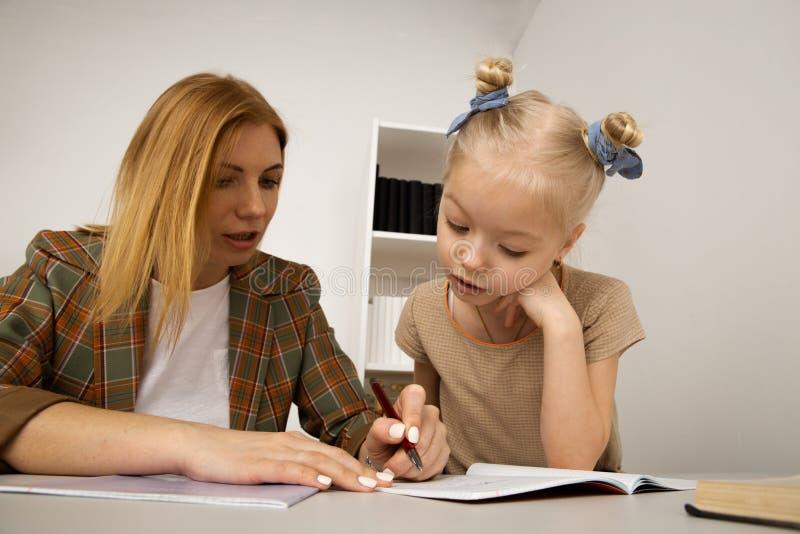 Bambino che studia con la madre allo scrittorio a casa immagine stock libera da diritti