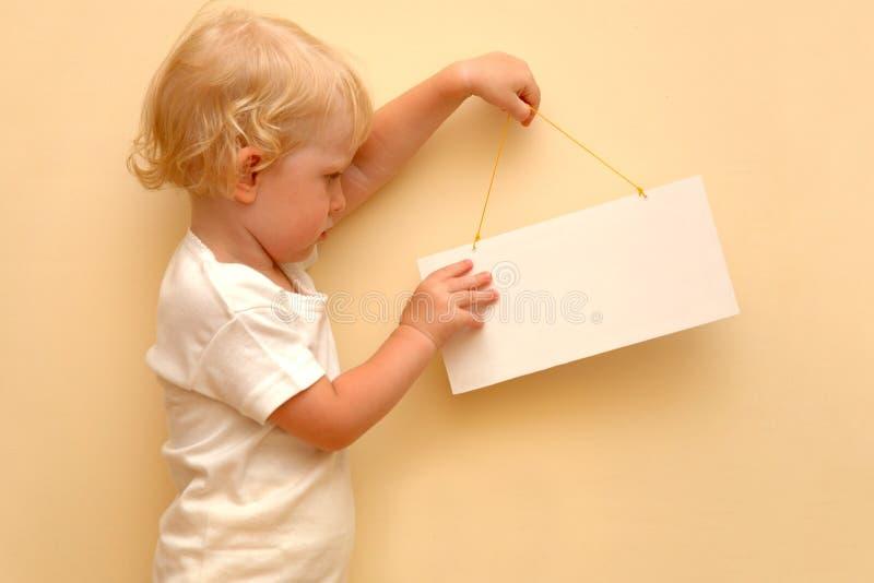 Bambino che tiene cartello in bianco fotografia stock libera da diritti