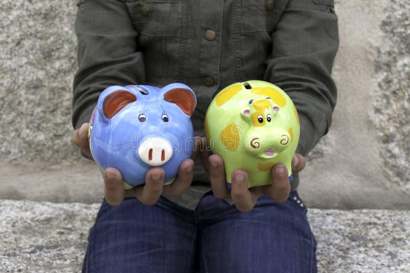 Bambino che tiene due contenitori di soldi II immagini stock libere da diritti