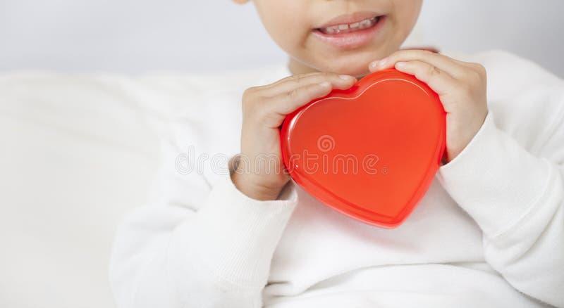 Bambino che tiene piccolo cuore rosso, primo piano fotografie stock